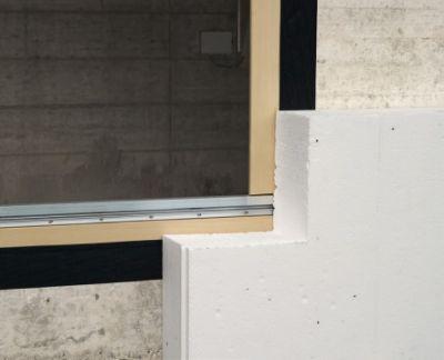 Szczelność wiatrowa i ochrona przed deszczem na zewnątrz – połączenie okna i ściany masywnej taśmą FENTRIM. Przykrycie łączenia warstwą ocieplającą.